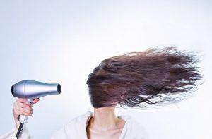 Eine Frau fönt sich die Haare